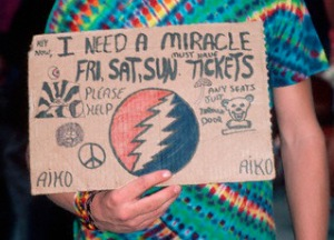 September 1987 --- A fan of the band Grateful Dead holds a handmade sign reading I need a miracle, hoping to get tickets to a Grateful Dead show. --- Image by © Lynn Goldsmith/Corbis